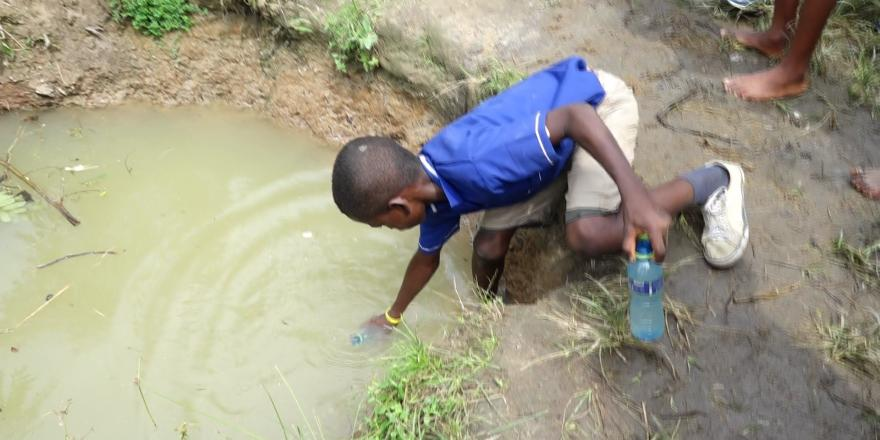 Young boy draws dirty water from pond